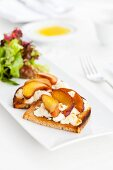 Rye bread topped with raw milk goat's cheese and plums