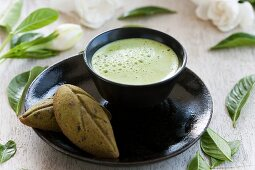 Matcha tea in a tea bowl, served with tea-flavoured madeleines
