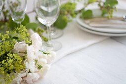 A table laid for a meal and decorated with white roses, baby's breath and ranunculus flowers