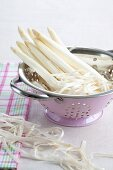 Peeled white asparagus in a colander