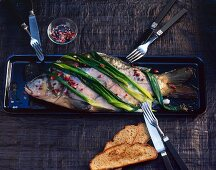 Carp au bleu with spring onions and red peppercorns