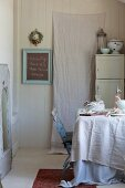 Linen cloths and crockery on table in vintage kitchen with white-painted cupboard and blackboard