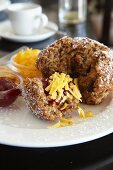 A bran muffin with jam and Cheddar cheese