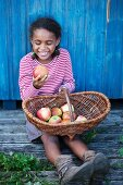 A laughing girl looking at an apple
