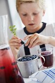 A boy with a glass of blueberry juice and fresh blueberries