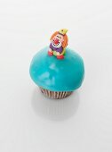 A turquoise cupcake decorated with a clown