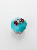 A turquoise cupcake decorated with ladybirds