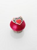 A cupcake decorated with a mouse couple and a heart