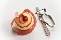 An apple with a knife and a peeler
