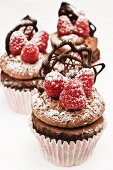 Chocolate cupcakes with raspberries and chocolate decoration