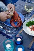 Boiled lobster with a bread roll and wine