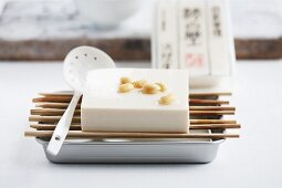 Silken tofu draining over an aluminium tray, with soaked soy beans