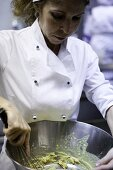 A chef stirring ingredients in a large bowl