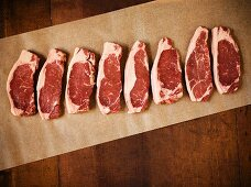 Raw Grass Fed New York Strip Steaks on Parchment Paper