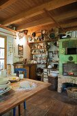Rustic kitchen with fireplace, wood-fired oven & shelves of kitchen utensils