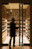 Person entering a modern wine cellar