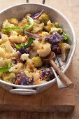 White and purple cauliflower with breadcrumbs in a baking tin on a wooden board
