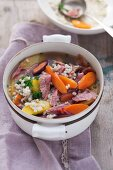 Mixed stew with meat, vegetables and barley in a white pot