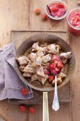 Kaiserschmarrn (shredded sugared pancake from Austria) in a pan with icing sugar, slivered almonds and strawberries, seen from above