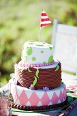 Decorated, tiered celebration cake with red and white flag