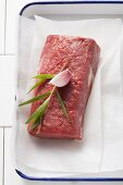 A fillet steak with tarragon and garlic on parchment paper in a roasting tin