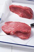 Steaks on baking paper in a roasting tin with a knife