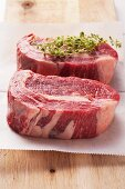 Two ribeye steaks on parchment paper with marjoram