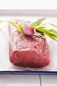Beef fillet with tarragon and a garlic clove on parchment paper