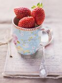 Strawberries in a floral-patterned cup