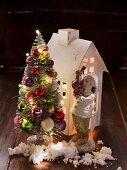 Paper house, porcelain figurine and artificial fir tree