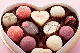 Various pralines in a heart-shaped box