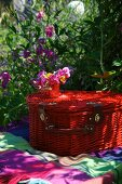 Red picnic basket on a blanket in the garden