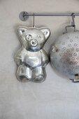 Bären-Backform und alter Metallseiher mit Fleischerhaken aufgehängt an Metallstange