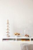 Moderne Etagere mit Schalen auf Holzstange, kleine Gebäckplatte und Käseglocke