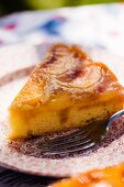 A Slice of Peach Upside Down Cake on a Plate; On a Sunny Outdoor Table
