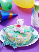 A cake decorated with a teddy bear for a baby party