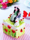 A child's birthday cake decorated with poppies, a girl and a dog