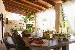A patio table laid for a snack on the veranda under a wooden roof