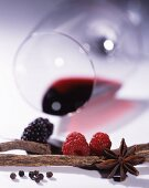 A glass of red wine lying on its side, with berries and spices