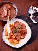 Chicken in chocolate sauce with a tomato and pumpkin medley