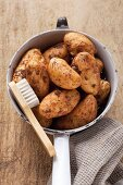 New potatoes in a colander with a brush