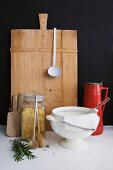 Vintage soup tureen and pasta in storage jar in front of chopping board leaning on black wall