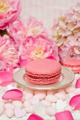 A pink macaroon on a silver plate, surrounded by sugared almonds, peonies and rose petals