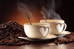 Two steaming cups of coffee and a pile of coffee beans