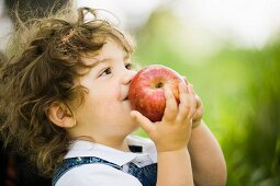 A small boy sniffing a large apple