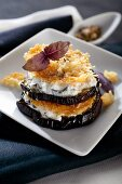 An aubergine tower with aubergine cream cheese and Parmesan chips