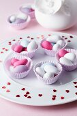 Sugared almonds in muffin cases on a plate scattered with hearts for a wedding