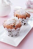 Muffins with icing sugar in cases with a flower pattern