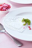Place setting decorated with doily, frog ornament & sugar hearts