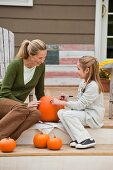Mother and daughter carving pumpkin